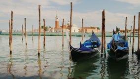 Символ Венеции традиционная шлюпка гондолы Тряхните на волнах, причаленных около берега Стоковое Изображение RF