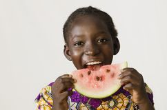 Символ голода - африканский ребенок наслаждаясь некоторым арбузом - изолят Стоковая Фотография RF