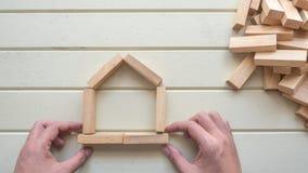 Символ дома и руки с деревянным блоком Стоковое Изображение