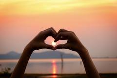 Символ руки сердца силуэта с предпосылкой захода солнца Стоковая Фотография RF