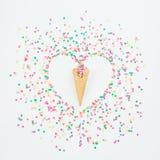 Символ сердца сделанный красочных confetti конфеты и конуса waffle на белой предпосылке Плоское положение, взгляд сверху Стоковые Фотографии RF