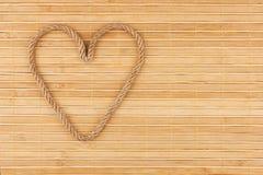 Символическое сердце сделанное веревочки лежа на бамбуковой циновке Стоковая Фотография