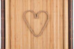 Символическое сердце сделанное веревочки лежа на furled бамбуковой циновке Стоковые Фотографии RF