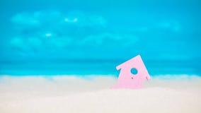 Символ маленького дома сирени на песке с яркой пасмурной синью покрасил предпосылку неба Стоковая Фотография