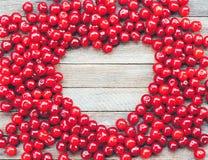 Символ сердца сделанный ягод вишни на деревянной предпосылке Стоковая Фотография RF