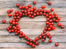 Символ сердца сделанный ягод вишни на деревянной предпосылке Стоковое Фото
