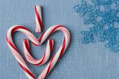 Символ сердца тросточки конфеты говоря сердце u I на голубой древесине с снежинкой Стоковая Фотография