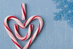 Символ сердца тросточки конфеты на голубой древесине с правильной позицией верхушки снежинки Стоковая Фотография RF