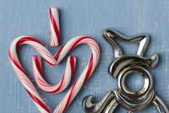 Символ сердца тросточки конфеты на голубой древесине с снеговиком Стоковые Фото