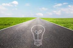 Символ электрической лампочки на длиной пустой прямой дороге Стоковые Изображения RF