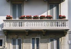 Симметричный балкон с баками красных цветков, в милане, Ломбардия Стоковое Изображение