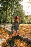 Симпатичная белокурая женщина в сером платье knit и красной шляпе сидя на th Стоковое Изображение RF