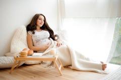 Симпатичная беременная женщина лежа в одеяле на белой кровати Стоковая Фотография