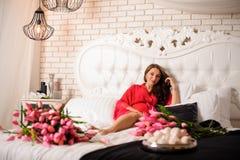 Симпатичная беременная женщина лежа на кровати с букетом цветков Стоковая Фотография RF