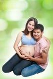 Симпатичная беременная с ее рукой используемой супругом касалась животу Стоковые Изображения