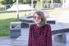 Симпатичная дама в стильных стеклах в парке стоковое фото