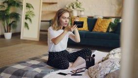 Симпатичная девушка использует косметики для того чтобы покрасить брови, она держит щетку и прикладывает состав смотря зеркало акции видеоматериалы