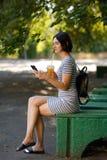 Симпатичная девушка сидя в парке Современная женщина с smartphone на предпосылке парка Социальная принципиальная схема средств ск стоковое изображение