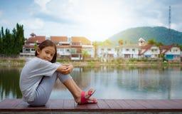 Симпатичная девушка сидя около естественного пруда с жилым массивом стоковое изображение rf