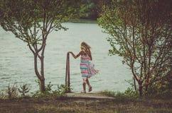Симпатичная девушка стоя на пруде в ветреной погоде стоковое изображение rf