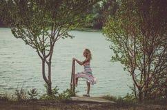 Симпатичная девушка стоя на пруде в ветреной погоде стоковая фотография