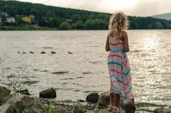 Симпатичная девушка стоя на пруде самостоятельно стоковые фото