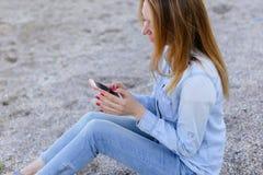 Симпатичная девушка тараторит на телефоне с улыбкой и сидит на пляже n Стоковые Изображения