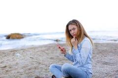 Симпатичная девушка тараторит на телефоне с улыбкой и сидит на пляже n Стоковое Изображение RF