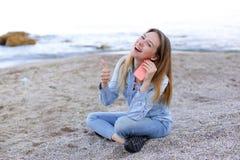 Симпатичная девушка тараторит на телефоне с улыбкой и сидит на пляже n Стоковые Изображения RF