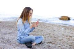 Симпатичная девушка тараторит на телефоне с улыбкой и сидит на пляже n Стоковые Фото
