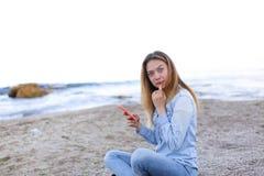 Симпатичная девушка тараторит на телефоне с улыбкой и сидит на пляже n Стоковые Фотографии RF