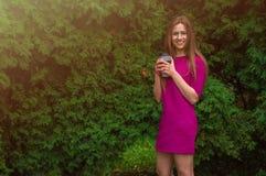 Симпатичная девушка в фиолетовом платье выпивает кофе в парке на su Стоковые Изображения