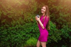 Симпатичная девушка в фиолетовом платье выпивает кофе в парке на su стоковые фото