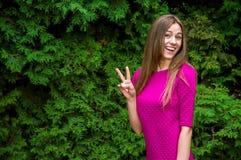 Симпатичная девушка в фиолетовом платье выпивает кофе в парке на su стоковые изображения rf