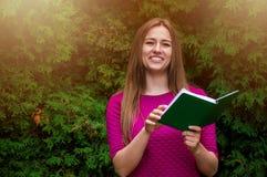 Симпатичная девушка в фиолетовом платье читая завораживающую книгу в стоковые фото
