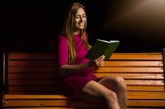 Симпатичная девушка в фиолетовом платье читая книгу стоковые фотографии rf