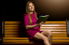 Симпатичная девушка в фиолетовом платье читая книгу стоковые изображения