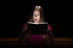 Симпатичная девушка в фиолетовом платье читая книгу Стоковые Фото