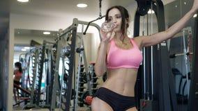 Симпатичная девушка держа бутылку воды в спортзале Стоковое Изображение RF