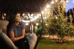 Симпатичная девушка задумчиво смотрит в сторону и усмехается сладостно, сидящ внутри стоковые фотографии rf