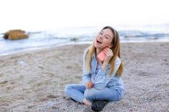 Симпатичная девушка тараторит на телефоне с улыбкой и сидит на пляже n Стоковое Изображение