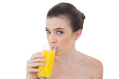 Симпатичная естественная коричневая с волосами модель выпивая апельсиновый сок Стоковое Изображение