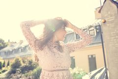 Симпатичная женщина брюнет в платье шнурка представляя на улице в лучах Стоковая Фотография