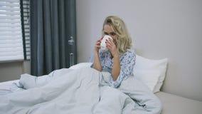 Симпатичная женщина выпивая в кровати сток-видео