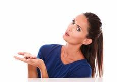 Симпатичная женщина в голубой рубашке держа ладони вверх Стоковая Фотография