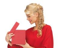 Симпатичная женщина в красном платье с раскрытой коробкой подарка Стоковое Фото
