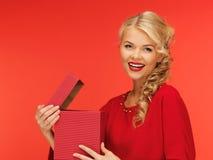 Симпатичная женщина в красном платье с раскрытой коробкой подарка Стоковая Фотография
