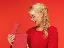 Симпатичная женщина в красном платье с раскрытой подарочной коробкой Стоковые Фото