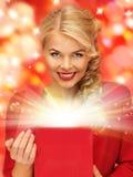 симпатичная женщина в красном платье с раскрытой подарочной коробкой Стоковое Изображение