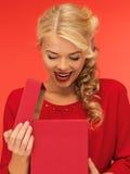 Симпатичная женщина в красном платье с раскрытой подарочной коробкой Стоковые Фотографии RF